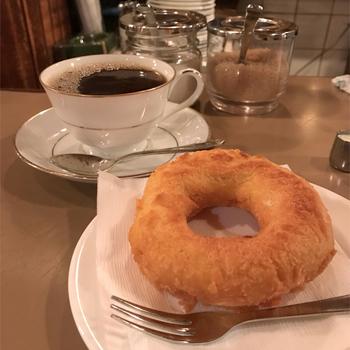 """名物の自家製のドーナツは、カリッと揚げられていて、ちょっと無骨なかたちが愛らしいですね。甘さ控えめで、素朴な味わい。まさに""""ザ・ドーナツという""""王道の美味しさ。"""