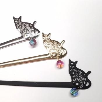 菊模様のレリーフが美しい猫のかんざしは、ちょぴり和テイストで、座った猫の姿がなんとも愛らしい雰囲気。 かんざし部分が一体化しているので、髪にからむことがなく、お出かけ中も、浴衣ヘアを可愛らしく演出してくれそうです。 ワンポイントで涼しげなガラスのビーズが付いているところも、さりげなくてとっても素敵!猫好きさんにはたまらないアイテムですね!