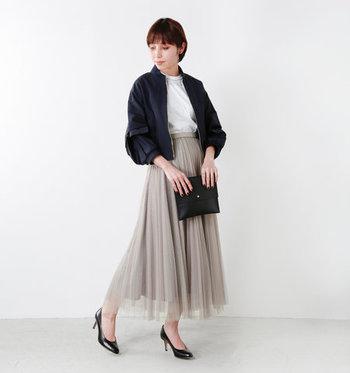 3層のチュールをプリーツ仕立てにしたロングスカートは、落ち着いたベージュカラーで大人っぽく。白のブラウス以外は黒で揃えて、モノトーンテイストのレディコードが完成です。ツヤ感のあるライトアウターが、レディ感をグッとアップさせていますね。