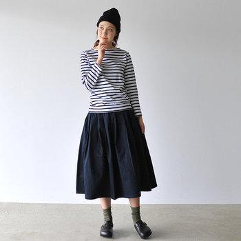 膝下丈のプリーツスカートは、ネイビーのボーダートップスと合わせて同系色でまとめた着こなしに。ニット帽やシューズもダークトーンでまとめて、秋らしさのあるカーキの靴下で季節感をプラスしています。