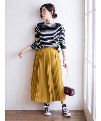秋らしいマスタードカラーのプリーツスカートは、ボーダートップスやスニーカーと合わせてカジュアルに。あえてチェーンバッグをチョイスすることで、カジュアルな中にもさりげなく女性らしさをアピールできます。スカートはウエストがゴムになっているので、タックインしやすいのも魅力。
