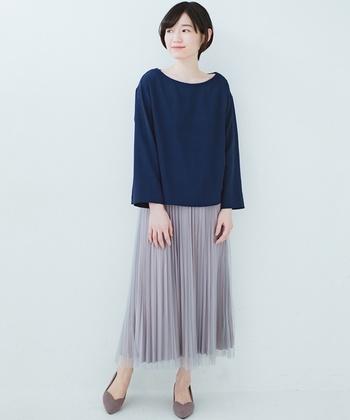 布とチュールが2枚重ねになっているプリーツスカートは、どんなトップスと合わせてもサマになる定番の一枚。グレーのスカートにネイビーのトップスを合わせて、カジュアルながらも上品な印象に仕上げています。