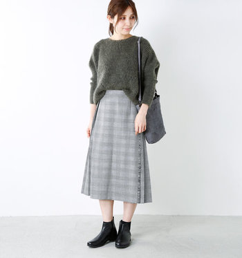 グレーのチェック柄巻きスカートは、サイドから後ろにかけてがプリーツデザインになっているアイテム。前と後ろでディテールの異なるスカートの雰囲気を楽しめます。秋らしいトラッド感のある着こなしにもぴったりな一枚ですね。