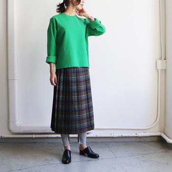 茶色ベースに青や緑のカラーをプラスした、チェック柄のタイトスカート。鮮やかなグリーンのトップスも、スカートの中に入っているカラーだからこそ浮かずにまとまりのある着こなしができます。寒い季節には、トレンドアイテムのレギンスを合わせるのもおすすめ。