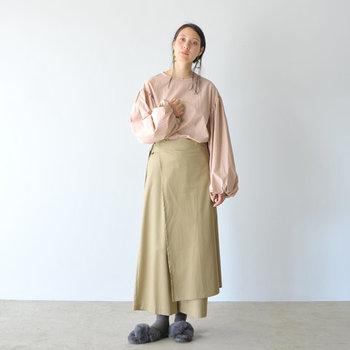 ピンクベージュのブラウスに、ベージュのワイドパンツを合わせたコーディネートです。ボリュームのあるブラウスのスリーブや、一見スカートのように見えるラップデザインのワイドパンツなど、個性的な着こなしが素敵ですね。ファーのサンダルを合わせて、季節感もプラス。