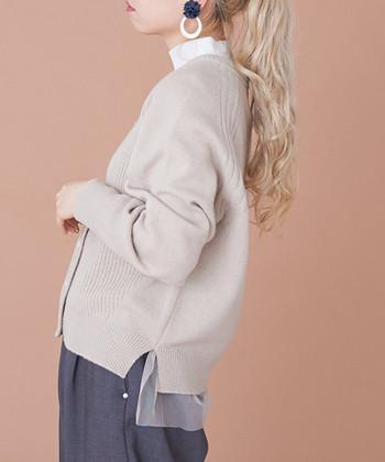 ベージュのVネックカーディガンの裾に、さりげなくチュールをあしらったデザインのニットアイテムです。前から見ると一見シンプルな印象ですが、よく見るとチュールがちらり。シックなコーデにもほんのりガーリーなアクセントをプラスできます。