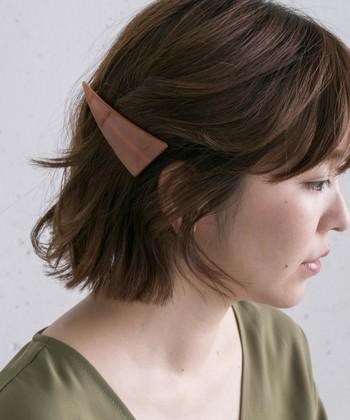 単調になりがちなダウンヘアを、横長バレッタで印象的な表情に。できるだけ耳の近くでパチッと留めるのがポイント。
