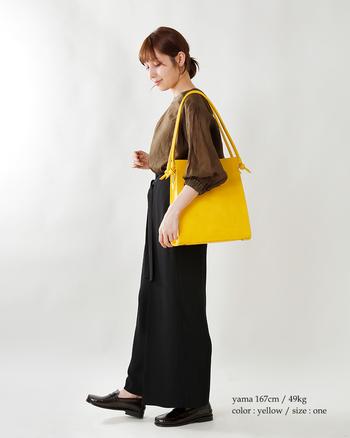 目が覚めるようなイエローのバッグは、シャープなアウトラインも印象的。ぼやけがちなブラウンとブラックの着こなしを、シャキッとキレよく仕上げてくれます。