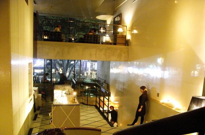 """大きな吹抜けや、2階には表参道のケヤキ並木を見おろすオープンテラスが。 """"囲まれ感""""のある少人数向けコーナーからソファ席まで多彩に揃い、変化に富む空間を演構成しています。家具から什器、照明器具に至るディテールへのこだわりも見飽きない*"""