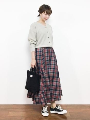チェックのスカートにカーデをトップス風に着たコーデは、大人でも照れずできるスクールガール風。トートバッグや定番スニーカーで、小物はさらりとシンプルに。