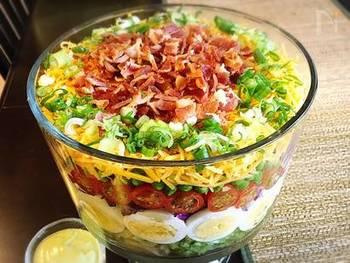 大きなボウルに材料を敷き詰めて重ねていくだけでできる豪華なパーティーサラダ。重ねる時にゆで卵やトマトの断面が外から見えるようにするのがポイントです。