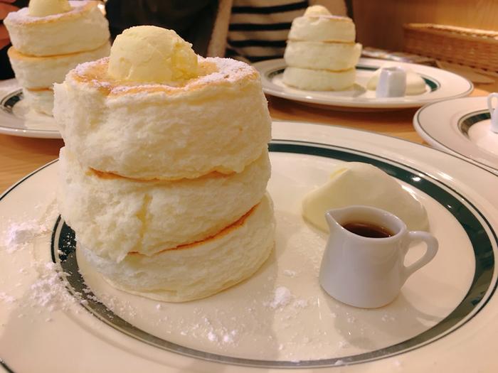 見ているだけでも、心が踊るふわふわ感♪1日3回の焼き上がり時に限定20食となっている「プレミアムパンケーキ」です。注文してから少し時間がかかる場合もありますが、店員さんが、焼きたてのパンケーキを慎重に運んできてくれますよ。  ふわふわの弾力がありながら、口に入れた瞬間にシュワっと溶けてしまう口当たりは、一度食べるとクセになる食感。3段に重なったパンケーキの上にはたっぷりのバターがトッピングされており、ホイップクリームとメープルシロップが添えられています。