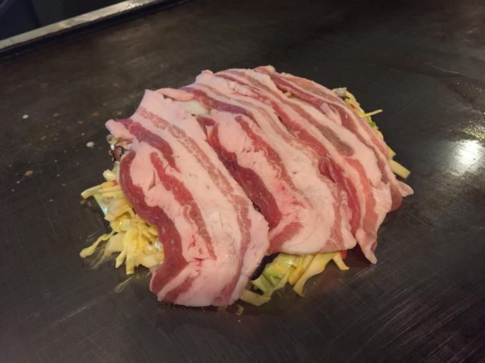 お好み焼きの代表はやっぱり『豚玉』。それにしても、こんなに大きな豚バラ肉をびっしり敷き詰めてあるなんて、ビックリ!「これが、カリッと焼けてメッチャ美味しいねん♪」