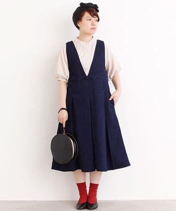 清潔感のあるネイビーのジャンパースカートは、上品な色使いでとことん品行方正な着こなしに。白いブラウスとレッドのソックスを持ってくれば、パリシックなトリコロール配色が完成します。