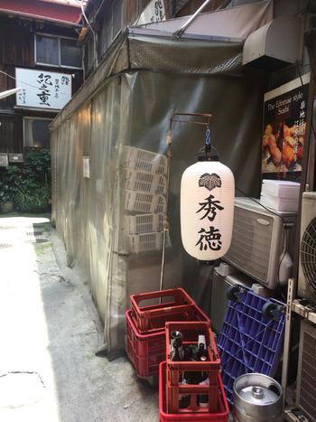 築地場外のお寿司屋さんの中でも、通好みとして知られている「築地秀徳 本店」は、都営大江戸線の築地市場駅から歩いて6~7分の路地裏にあります。土日にお休みが多い築地界隈で土日とも営業していることもあり、いつも大勢のお客さんでにぎわっています。