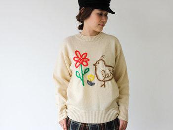 ざっくりとしたベージュのセーターに、鳥や花のゆるいイラストが刺繍されたアイテム。首が詰まっているシルエットが今ドキ。柄物のボトムスと合わせて、とことんおしゃれに着こなして。
