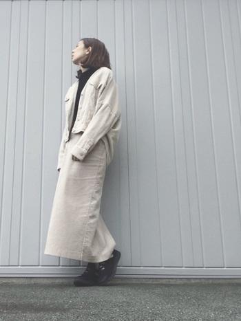 淡いベージュのブルゾンにロングスカートを合わせたセットアップ風コーデ。やわらかな色に黒いインナーをinして、引き締め役に。
