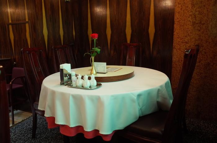 円卓にシックな椅子、真ん中にバラの花。このセッティングだけで高級感と老舗の風格が感じられます。