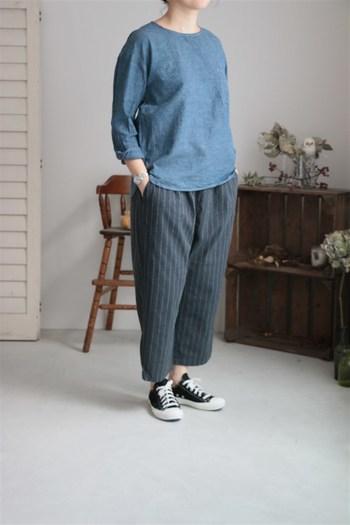 グレーのストライプパンツは、メンズライク or ボーイッシュに着こなすのがセオリー。淡いブルーのプルオーバーをセットしたら、足元はスニーカーで少年っぽくまとめて。