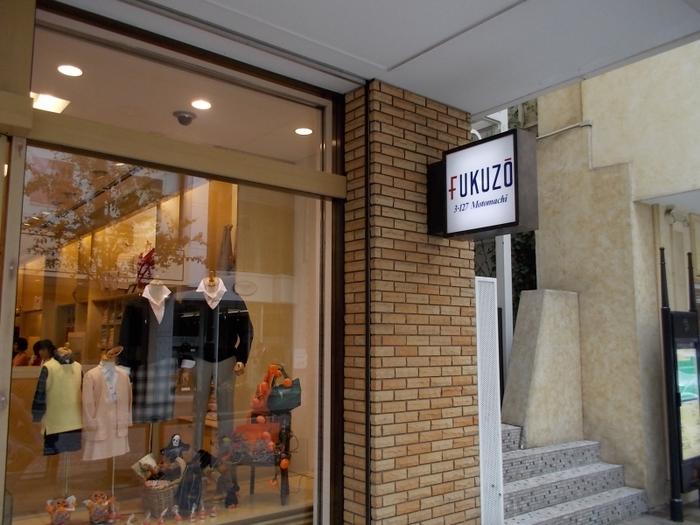 1946年元町でお店を構えてからずっと愛され続けている「フクゾー洋品店」。生地や糸、染色、裁断、縫製まですべてオリジナルの「メイドインジャパン」のこだわりの製品を作り続けています。洋服は、時代の空気を取り込みながらも、初代や二代目の考案したベーシックなデザインを継承。「タツのおとしご」のマークがフクゾーのポイントです。