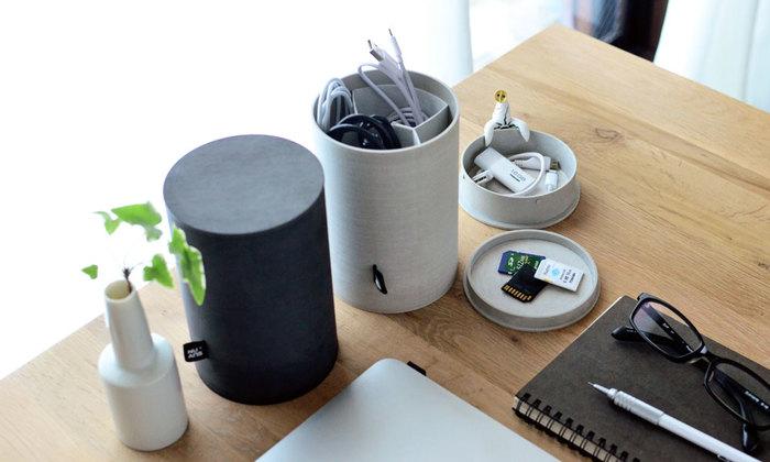 こちらの白と黒の円柱のシンプルな収納ケース「CADDY(キャディー)」は、パソコンやスマホ、タブレットなどのケーブル類やメディアカードなど、小さくて散らかりがちな物を収納するために開発された小物入れなので、蓋を開けると内部 に可動式の仕切りが付いており、円筒の底面にも収納が付いています。