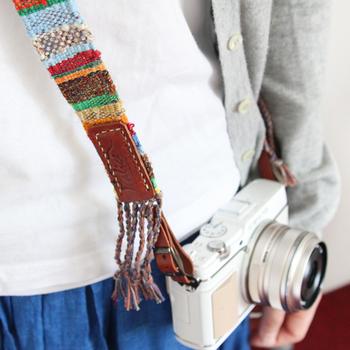 カメラに装着すると、こんな風にストラップの下の部分にはフリンジが施され、遊び心も忘れません。 パッと明るいカラーは、色見を抑えたお洋服や、ジーンズに白いTシャツといったナチュラルコーデにも映えそうですね!