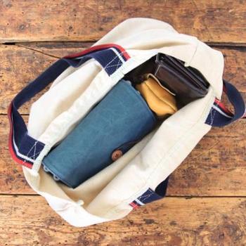 """表地にはテントやトラックの幌などに使われる""""パラフィン加工""""という防水加工を施した帆布を使用。綿素材にコーティングすることで撥水性も抜群。使いはじめは少し生地に硬さがありますが、使い込んでいくうちに、柔らかく素材本来の風合いがより楽しめます。普通のバッグにカメラを直接入れるのはちょっと…そんな人達にとっては、まさに「あったらいいな!」のアイテムですね!"""