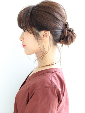"""まとめ髪の定番お団子ヘアも、オフィスアレンジでは""""低め""""が正解!耳から上の髪をお団子にして、残りの髪をねじって巻きつければ完成。後頭部の髪をつまんでトップにボリュームを出すことで、横から見たときも美しく。きちんとした印象が大切なので、後れ毛は少なめに◎"""