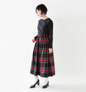 ミディ丈のボリューム感あるチェック柄スカートも、黒のトップスを持ってくることでキリっと引き締まります。ソックスと太めヒールのパンプスがなんとも素敵なクラシカルな雰囲気を醸しだしています。
