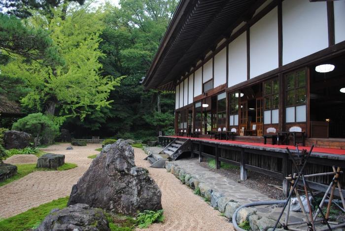 """【花の寺""""として良く知られ、広い寺内では、水芭蕉やツツジ、ヤマユリや蓮、秋明菊等など、春から秋にかけて様々な花々が咲開くが、秋の紅葉、冬の雪景色も素晴らしく、禅寺ならではの庭園も味わい深い。(画像は、山内随一の建物である本堂と、禅寺ならではの枯山水庭園。)】"""