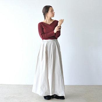 白のロングスカートは春夏のイメージが強いアイテムですが、秋色ボルドーの薄手ニットを合わせれば、秋にも着回しOKのコーディネートが完成します。トレンド感のあるワイドリブニットは、バックデザインが深めに開いているのもワンポイントに。