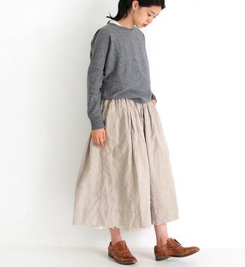 シンプルなクルーネックの薄手セーターは、リネン素材のボトムスとも好相性。ニットのインにはノースリーブのブラウスを合わせて、首元からちらりと見えるブラウスの襟がこなれ感を演出するワンポイントになっています。