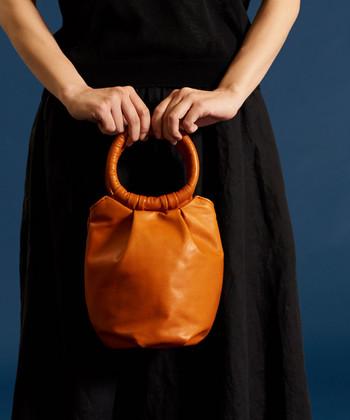レザー素材の小ぶりな大人っぽいバッグは、丸いハンドル部分にもくるくると皮を巻き付けた個性的なデザイン。どんなファッションにも合わせやすいブラウンを選べば、様々な場面で活躍してくれること間違いなしのアイテムですね。