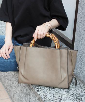 大きめのトートバッグに、バンブー素材のハンドルがアクセントになっているアイテム。落ち着いたチャコールグレーのバッグにバンブーが合わさると、秋らしいカラーリングで季節感をしっかりアピールできます。
