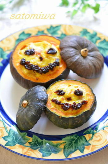【坊ちゃん南瓜のマカロニグラタン♪】 かぼちゃを丸ごと使ったグラタンレシピ。ウインナーやマカロニ入りのグラタンを器に見立てたかぼちゃに詰めて焼き上げています。ジャック・オー・ランタンの顔は海苔の佃煮で作っていますが、他の食材で代用しても◎