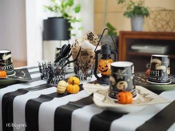 シンプルなモノトーンのストライプ柄の布をテーブルクロスにして、かぼちゃのオレンジを差し色に、その他の小物を黒で統一するだけでもハロウィンらしい雰囲気に。