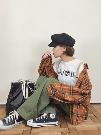 秋の定番チェック柄。オレンジブラウンのビッグシャツでリラックス感のあるハロウィンスタイルに。バッグ・スニーカー・帽子など黒の小物で、クールに引き締めています。