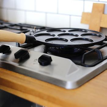 鋳鉄と木のハンドルの組み合わせが魅力的なパンケーキパンは、北欧スウェーデン、GENSE社のパンケーキパン。 GENSEといえば、スウェーデン王室御用達の老舗メーカーで、カトラリーはノーベル賞晩餐会で使用されていることでも有名。 パンケーキというと、薄めに焼いた生地を何枚も重ねて食べるのも醍醐味ですが、フライパンやホットプレートで、揃えた大きさのものを焼こうとしても、意外と大変で、時間もかかりますよね… そんな時、こちらのパンケーキパンなら、生地が一気に7枚焼けるので、とっても重宝するんです!