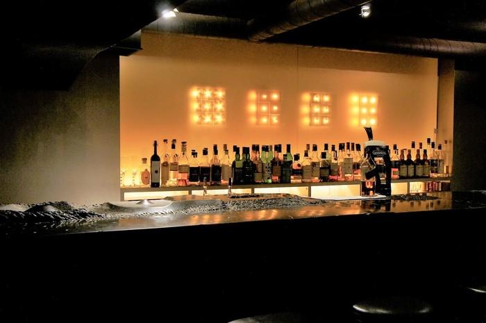 やさしい灯りがシックな店内では、ひとりでゆっくりとお酒を楽しむ方も多いんですよ。重厚な黒大理石のカウンターは、まるで大地のよう。