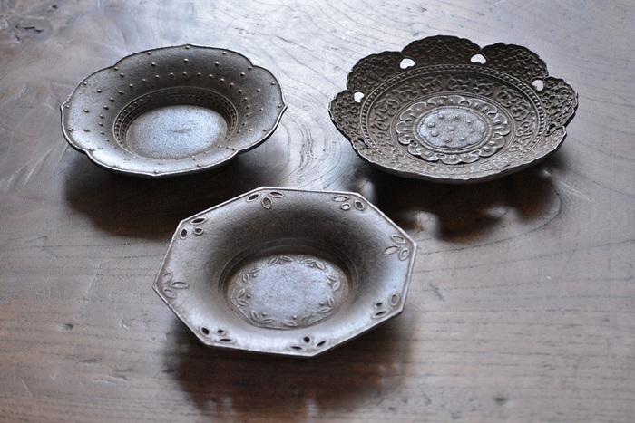 伝統的な図柄と、独特の錆色が魅力の美しい茶托。こちらも鉄瓶と同じく、鈴木盛久工房の作品です。写真右上から時計回りに、中尊寺金色堂の天蓋模様を模した「天蓋茶托」、素朴な透かし模様が美しい「八角」、花びらのような上品なフォルムが特徴の「霰(あられ)」です。