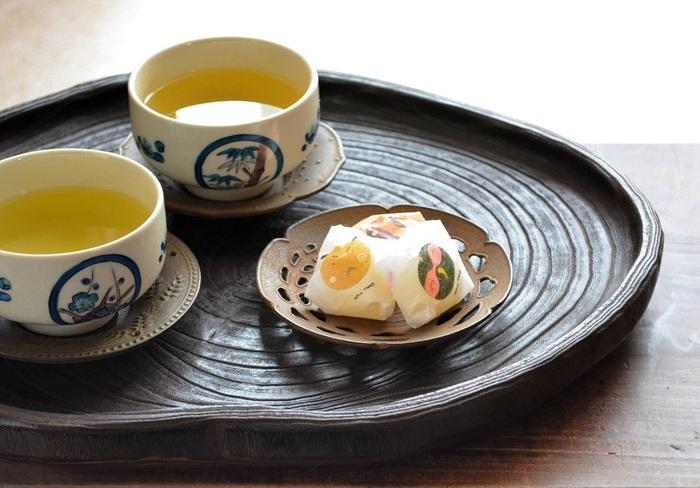 手前右側の茶托は、繊細な藤の透かし紋様をあしらった「藤すかし」、左側は麦の穂をモチーフにした素朴な雰囲気の「麦」。どちらも独特の落ち着いた風合いと、味わい深い錆色が印象的です。茶托としてはもちろんのこと、写真のようにお菓子をのせる銘々皿としても使用できます。