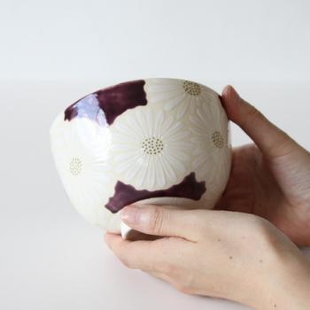 京都を代表する伝統工芸品、「清水焼」。日本古来の美意識を感じさせる繊細な図柄と、美しく艶やかな色彩が特徴です。白い菊が描かれた上品な抹茶椀は、これからの季節の茶会にぴったり。深みのある紫地に映えて、とても綺麗ですね。