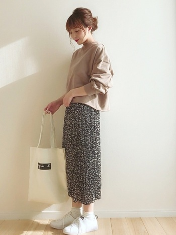 女性らしく髪をまとめて、プリーツスカートをあわせればスウェットアイテムも一気に女顔。無地のトップスならちょっぴり派手なスカートがかわいい。靴下をあわせれば今っぽくなります。