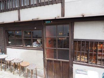 """""""隠れ家的パン屋さん""""といえばここ「ネコノテパン工場」。坂道を上がって住宅街のなかにひっそりとある、まるで絵本に出てくるような小さなかわいいパン屋さんです。店内は大人がひとり入れるくらいの小さなスペース。お店の外には可愛らしい丸椅子も用意されていて、待っている時間もどきどき。噂を聞きつけてやってくるお客さんがお店の外に並んでいます。"""