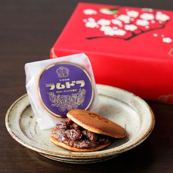 手焼きの薄皮に、北海道産の大納言小豆で作った餡を挟んだラムドラは、その名の通り、ラムレーズンをたっぷりサンドしたどら焼きです。ラム酒の芳醇な香りが口に広がる、大人の味わいです。