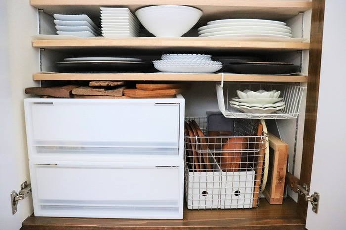 食器棚をスッキリ見せる方法は、食器の種類ごとに重ねて収納すること。同じお皿同士だと何枚重ねても1つにまとまって見え、逆に違うお皿だと一枚一枚がバラバラに見えてきます。小さい食器や、色・形がバラバラな食器は、引き出しやカゴなどの収納用品を使って、まとめてあげると◎
