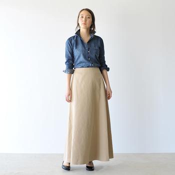 ウォッシュの効いたデニムシャツに、上品なベージュのロングスカートをセット。佇まいを優雅に見せる長めの丈感で、リラクシーなムードの中にもしっかりと女性らしさが共存。