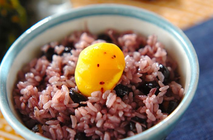 じっくりと炒ってだし汁に浸けた黒豆を、お米ともち米とともに炊飯器で炊き上げます。栗の甘露煮を焼いたものを添えると、より風味もよくきれいです。ちりめんじゃこも、いい味のポイントになります。