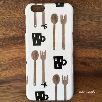 ブラウンとブラックで描かれた木目風デザインの北欧カトラリーに、カフェでくつろいでいるときのようにホッとした気持ちになれるスマホケース。黒いマグカップにさりげなく描かれているモミノキも可愛いですね。