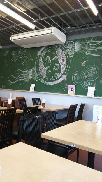 黒板アートが描かれた店内。4人がけのテーブルが多く置かれているので、ゆっくりと過ごすことができます。